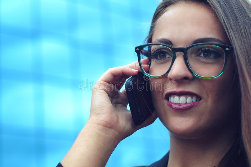 Businesswoman talking cellular phone outside building stock photo