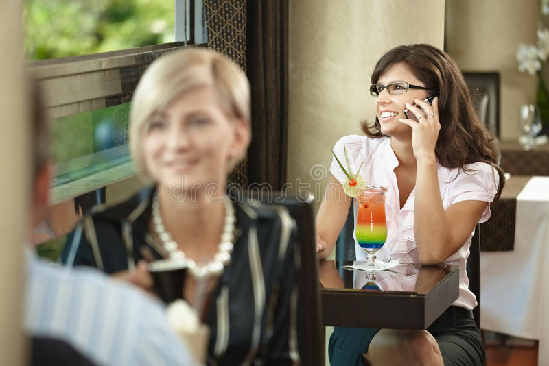 Businesswoman talking on mobile in cafe stock photography