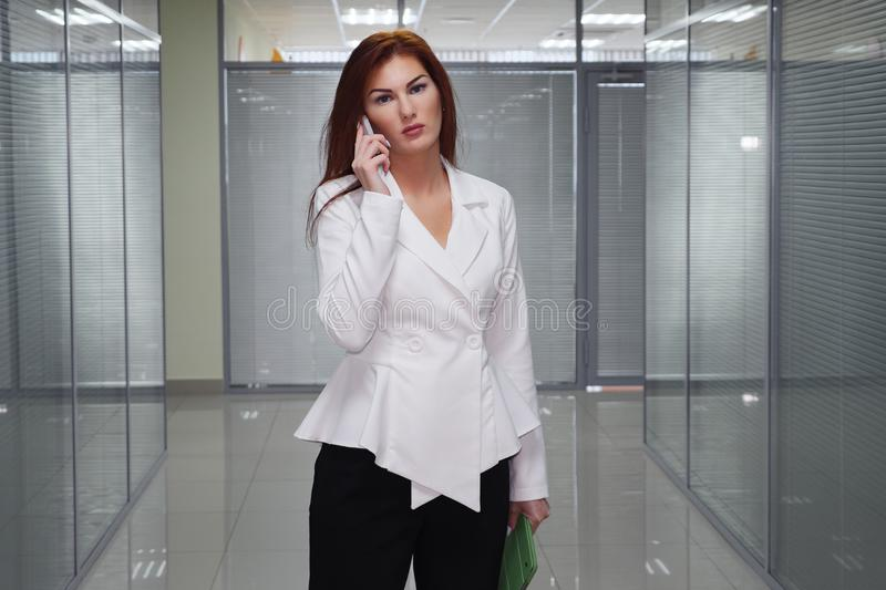 Businesswoman talking on the mobile phone in corridor of office royalty free stock images