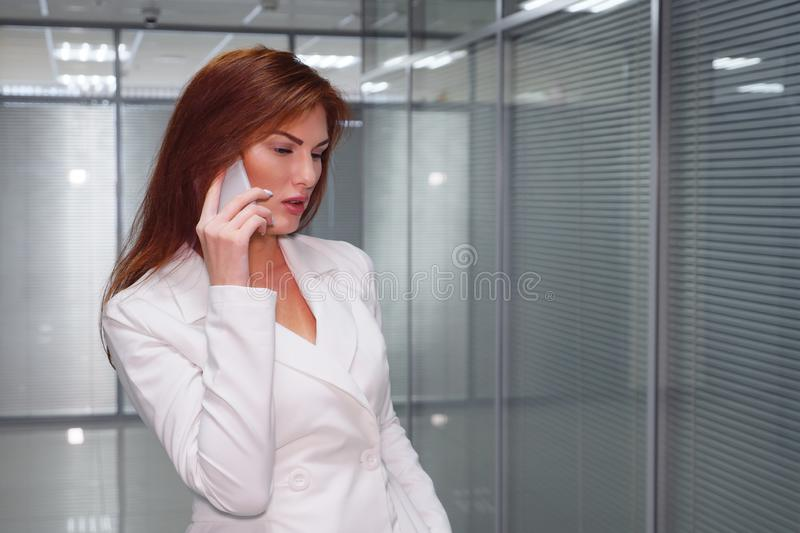Businesswoman talking on the mobile phone in corridor of office royalty free stock photo