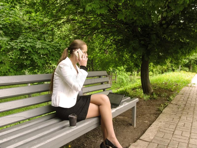 Businesswoman talking on mobile, sitting on a bench with a laptop and coffee in the park, side view. Young long-haired woman in. Glasses does business enjoying royalty free stock image