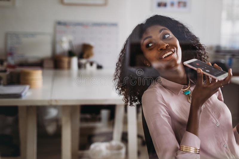 Businesswoman talking over mobile phone on loudspeaker while wor stock photo