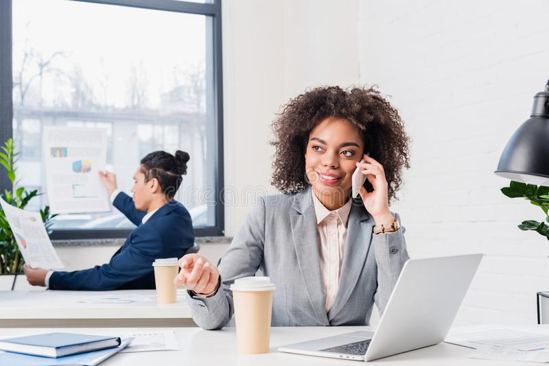 Businesswoman talking on phone with businessman working stock photo