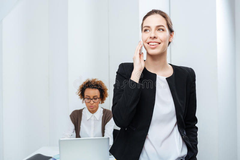 Businesswoman talking on phone while her colleague working with laptop royalty free stock image