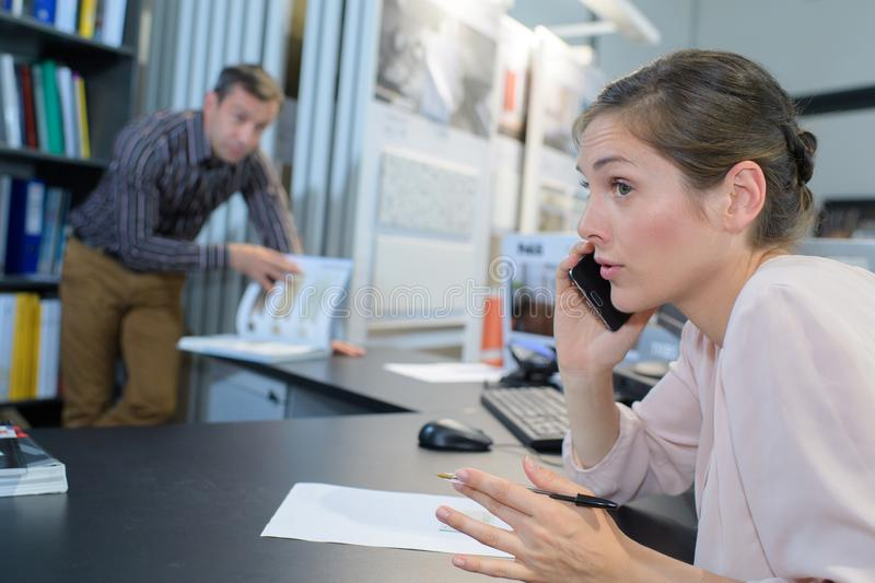Businesswoman talking on phone in office stock photography