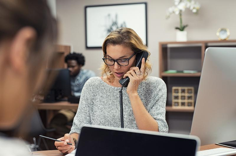 Businesswoman talking on phone at office stock photo