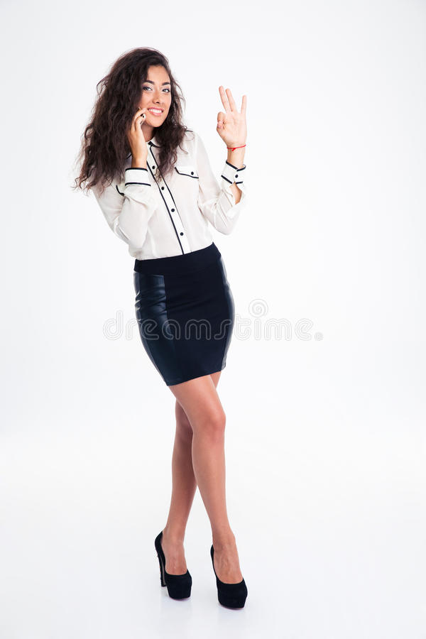 Businesswoman talking on the phone and showing ok sign royalty free stock photography