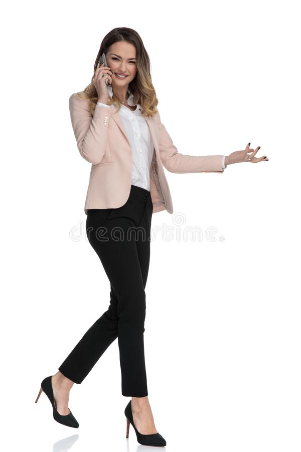 Businesswoman talking on the phone walks and presents to side royalty free stock photography
