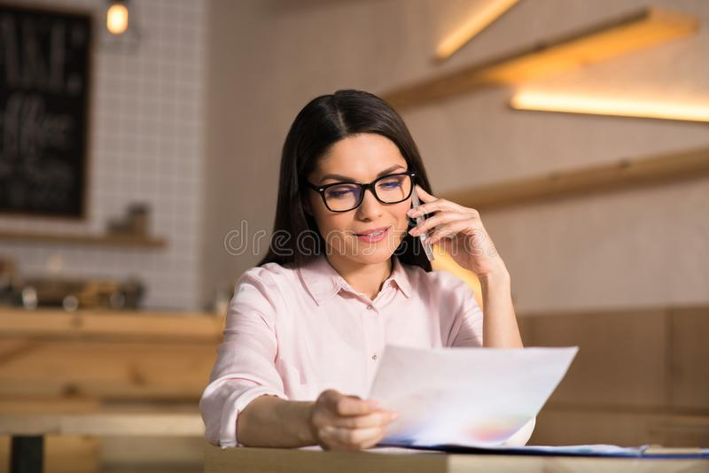 Businesswoman talking on smartphone. Cheerful businesswoman wearing eyeglasses talking on smartphone and holding document in cafe stock photos