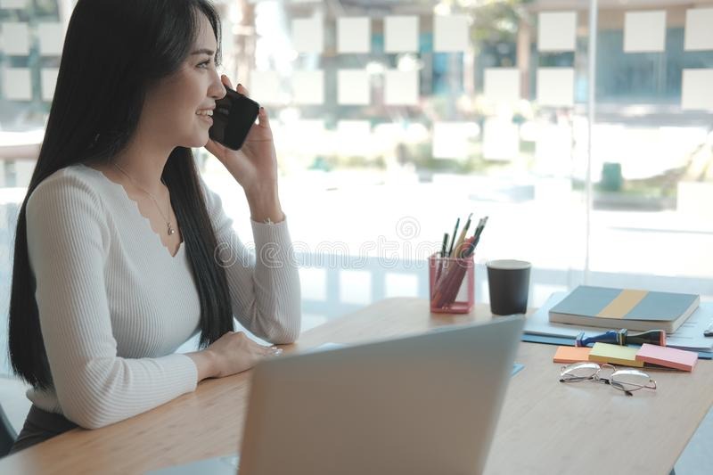 Businesswoman talking on smartphone at office. freelance woman using mobile phone. business concept royalty free stock images