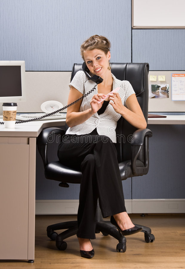 Businesswoman talking on telephone. Sitting at desk royalty free stock images