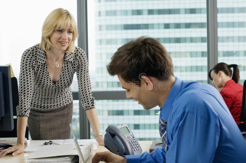 Businesswoman talking to businessman sitting at desk in office, woman working beside window stock photos