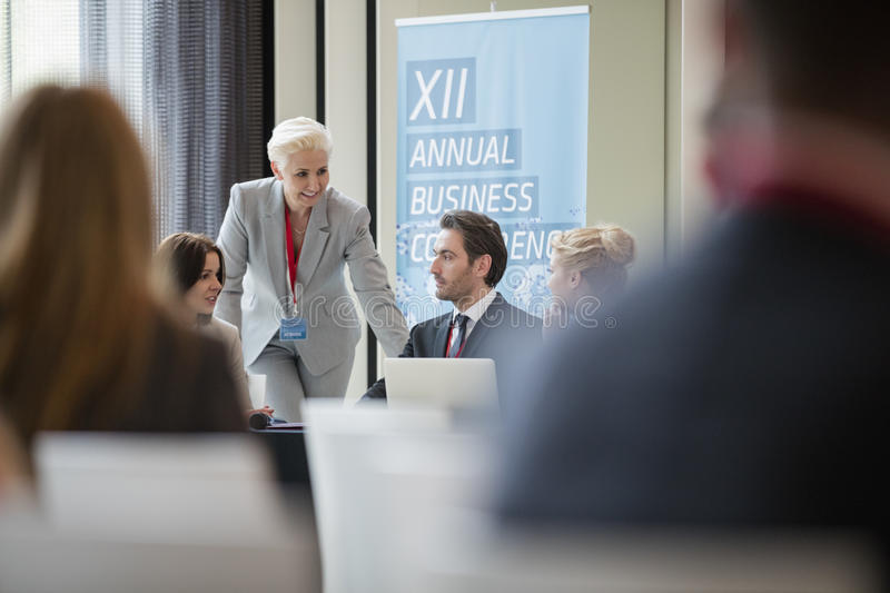 Businesswoman talking to colleagues during seminar stock photos