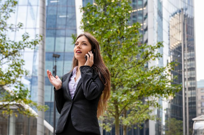 Businesswoman talks on mobile phone in front of modern office buildings. Young, confident businesswoman in corporate outfit talks on mobile phone outdoors in royalty free stock image