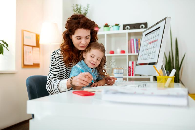 Businesswoman teaching her cute funny daughter writing letters. Daughter writing letters. Prosperous young businesswoman teaching her cute funny daughter writing royalty free stock image