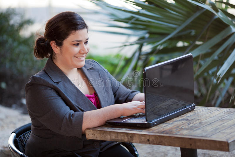 Businesswoman - Telecommuting from Internet Cafe. Stock photo of a well dressed businesswoman looking down at a laptop while telecommuting from an internet cafe stock images