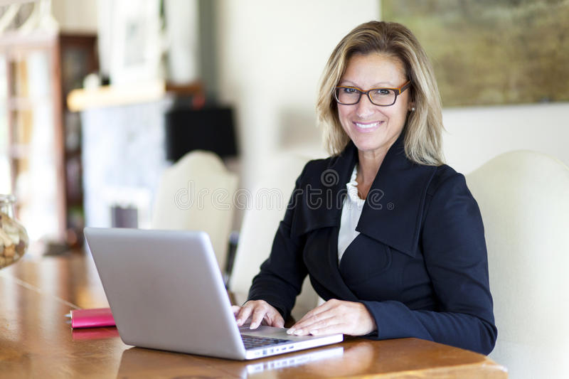 Businesswoman teleworking at home. On a Laptop. Smiling stock images
