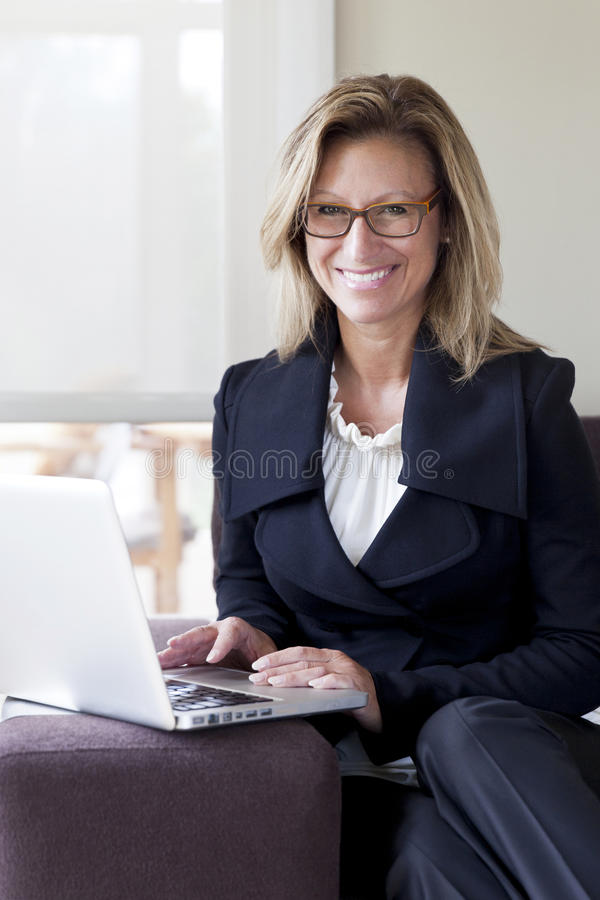 Businesswoman teleworking at home. On a Laptop. Smiling stock photos