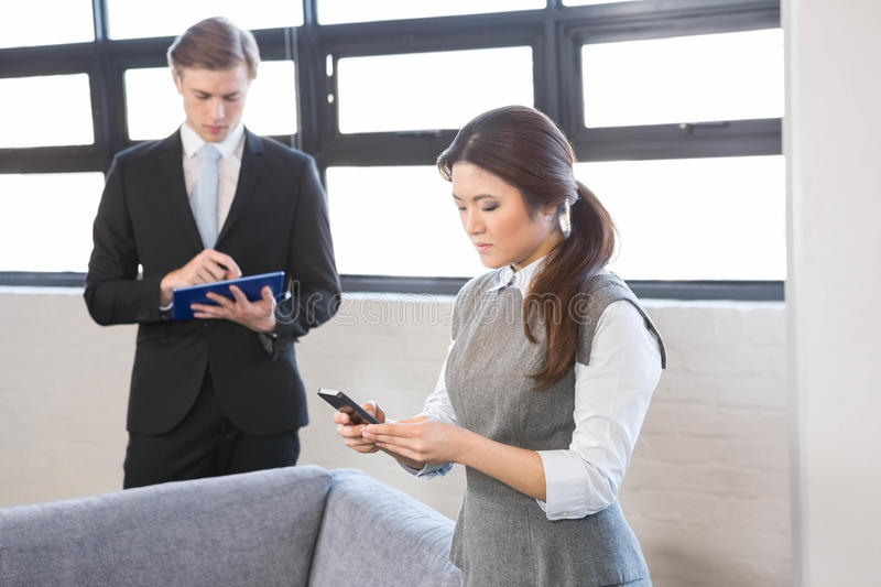 Businesswoman text messaging on smartphone and businessman using digital tablet stock image