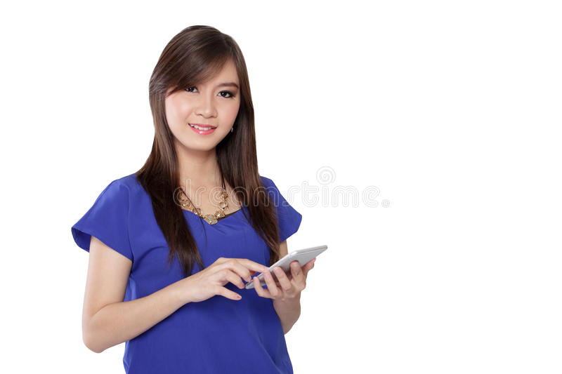 Businesswoman texting on smartphone. Young Asian bussinesswoman touch a smartphone screen and smile at camera, isolated on white background royalty free stock image
