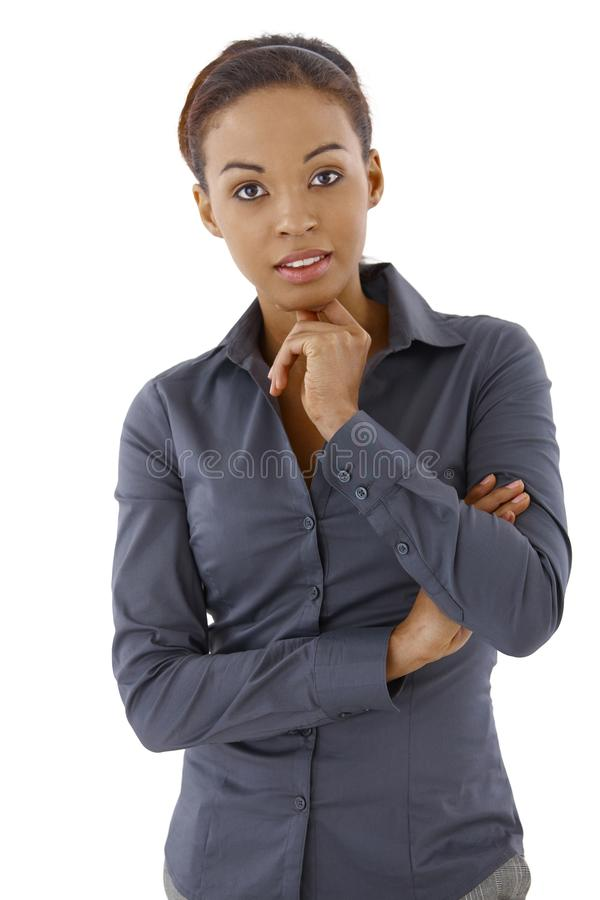 Businesswoman thinking. Standing in studio, looking at camera stock images