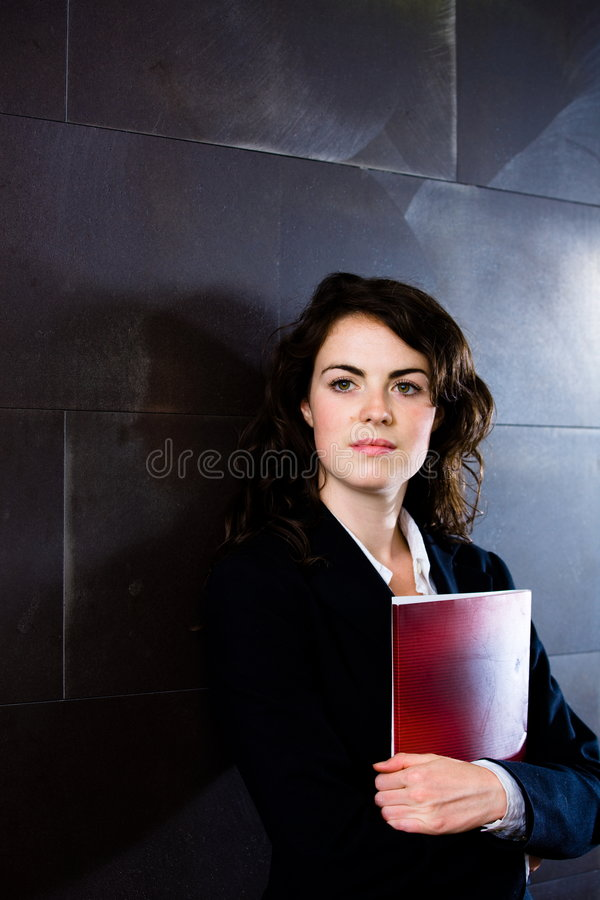 Businesswoman thinking. Young businesswoman in dark suit holding red folder daydreaming on office corridor posing for business portrait royalty free stock images