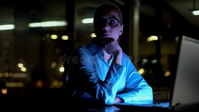 Businesswoman thinking of difficult business project, working extra hours, night stock photography