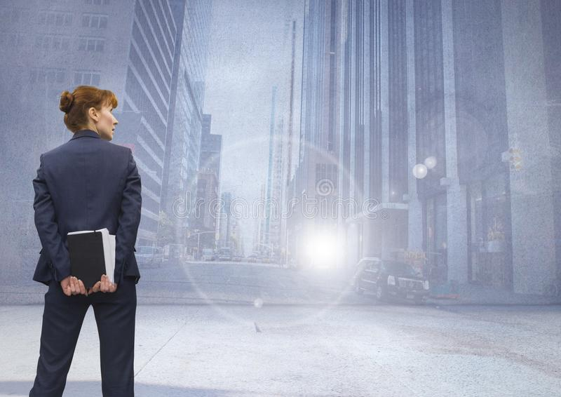 Businesswoman thinking in front of city street stock image