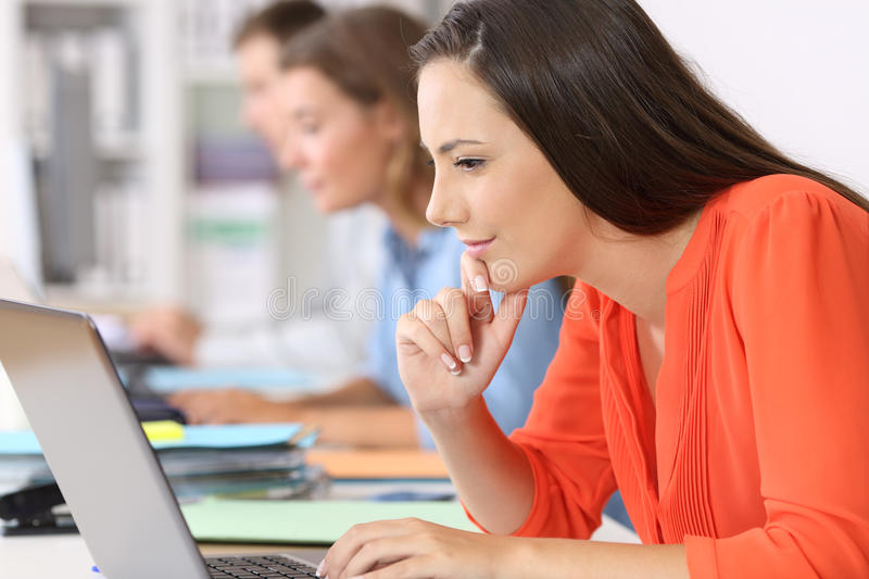 Businesswoman thinking with a laptop at office stock images