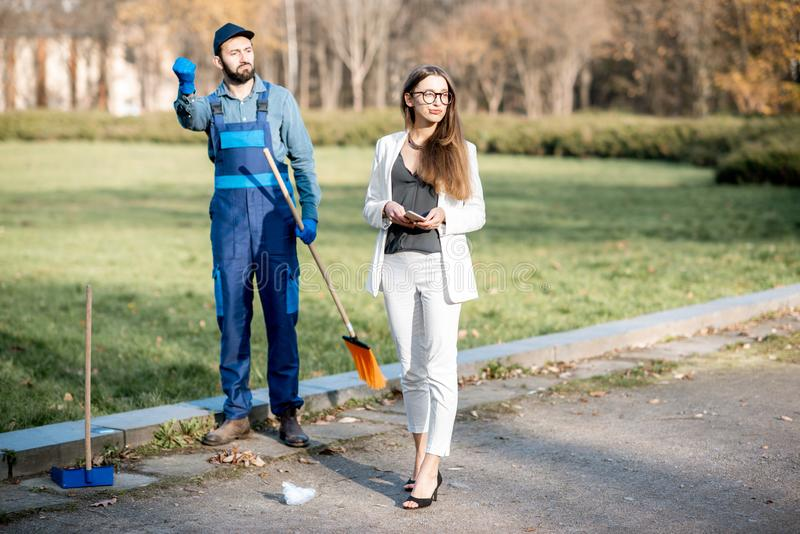 Businesswoman and sweeper in the park royalty free stock photography