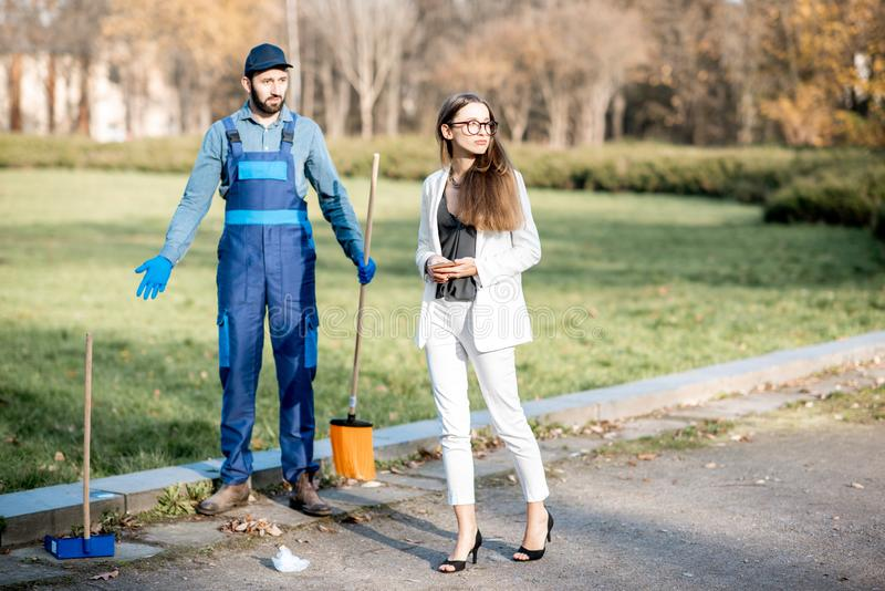 Businesswoman and sweeper in the park stock photo