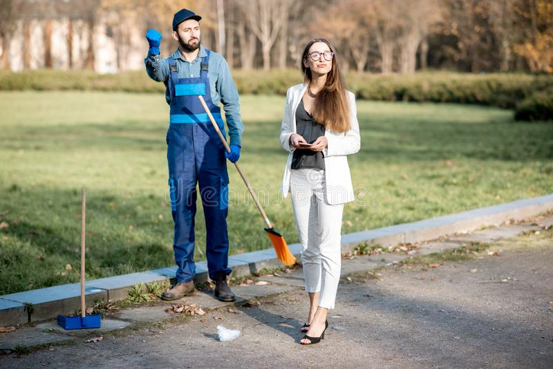 Businesswoman and sweeper in the park stock image