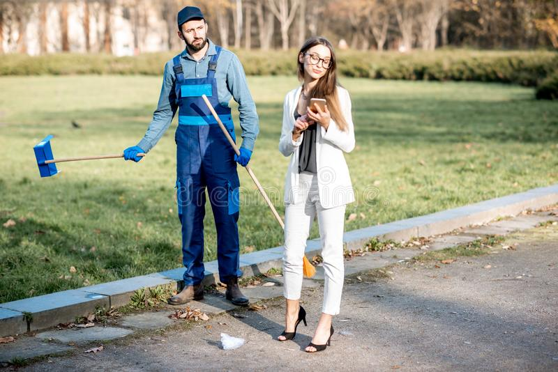 Businesswoman and sweeper in the park stock images