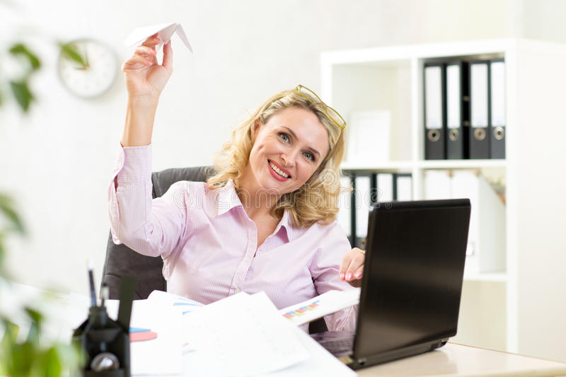Businesswoman throwing paper airplane in office stock photography