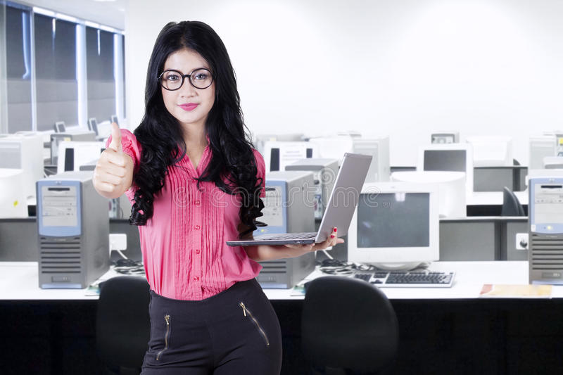 Businesswoman with thumb up in office room. Young businesswoman with long hair, standing in the office room while showing thumb up and holding a laptop royalty free stock photo