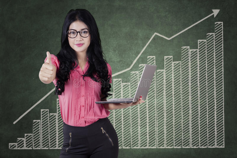 Businesswoman with thumb up and a profit graph. Successful young businesswoman showing a thumb up and holding a laptop with a profit graph background royalty free stock photos