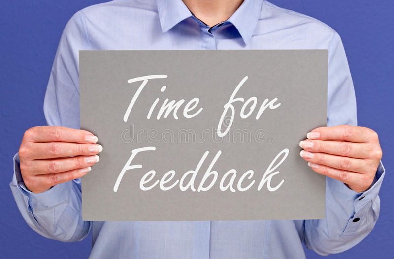 Time for feedback. Businesswoman with time for feedback sign in the office - business, presentation, meeting, workshop or seminar concept image stock image