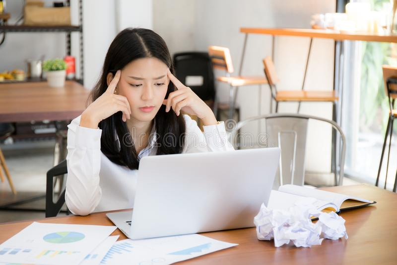 Businesswoman tired and stressed with overworked at desk, woman asian with worried not idea with graph analysis laptop. stock photo