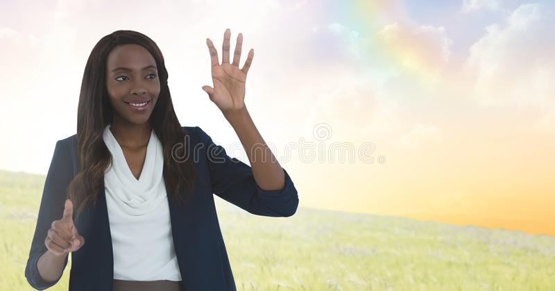 Businesswoman touching air in front of meadow clouds. Digital composite of Businesswoman touching air in front of meadow clouds royalty free stock photography