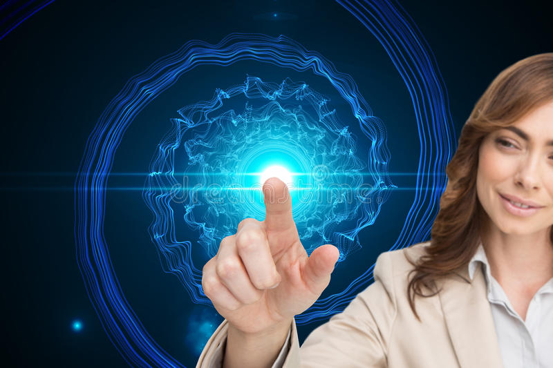 Businesswoman touching invisible screen. Composite image of businesswoman touching invisible screen stock photo