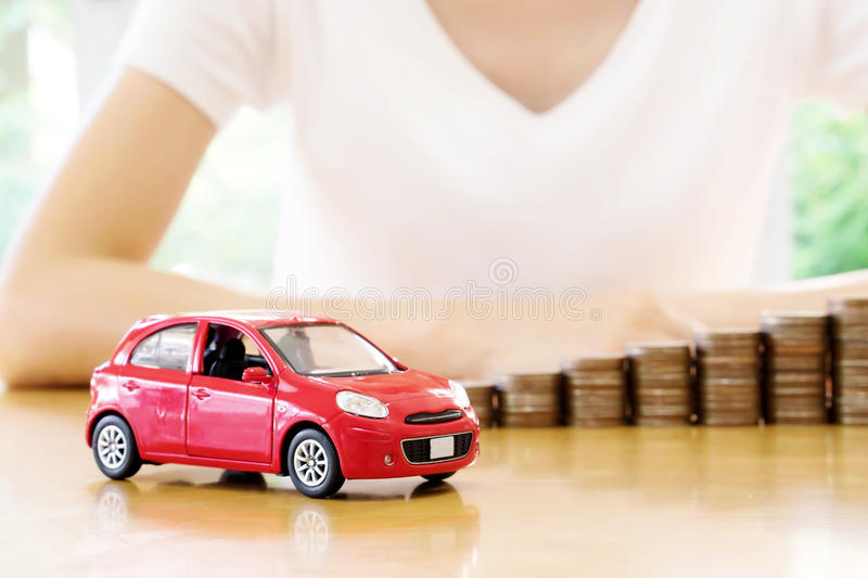A Businesswoman a toy car and a stack of coins. Businesswoman a toy car and a stack of coins royalty free stock image