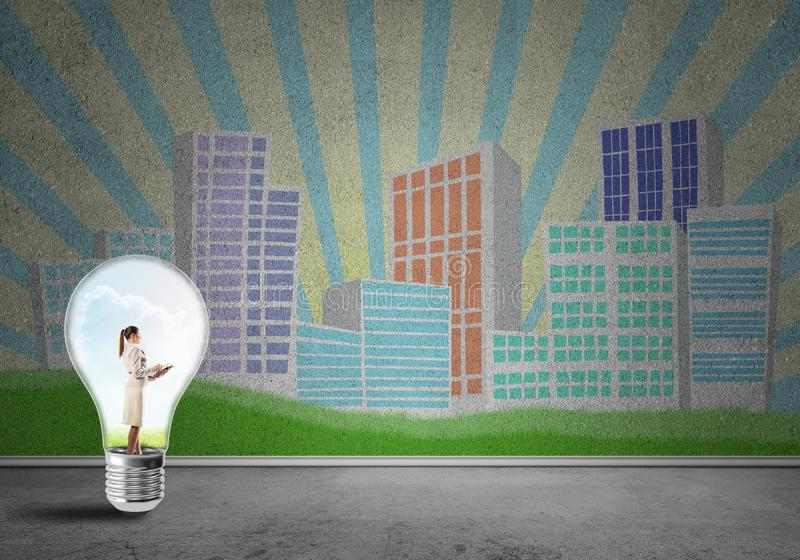 Businesswoman trapped in bulb royalty free stock photo