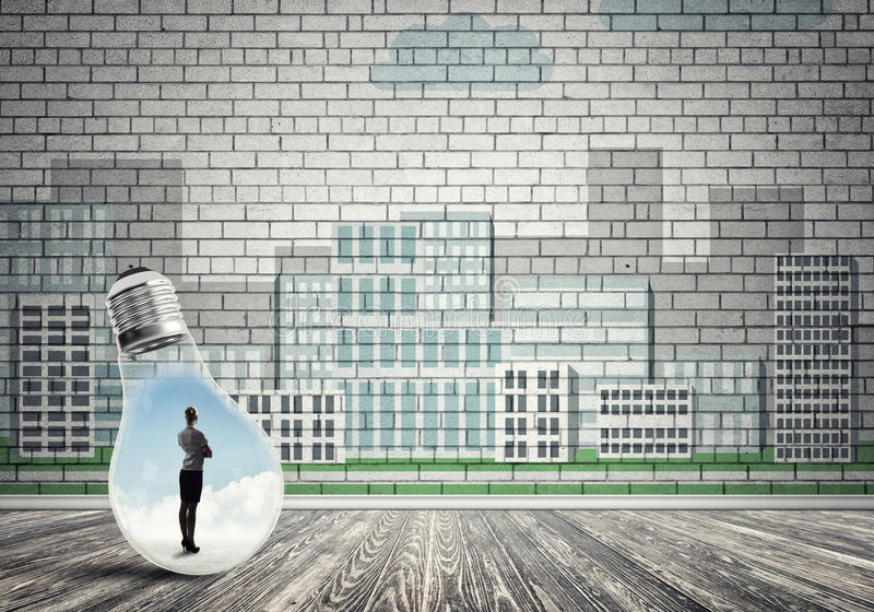 Businesswoman trapped in bulb. Businesswoman inside light bulb against city drawn concept stock photography