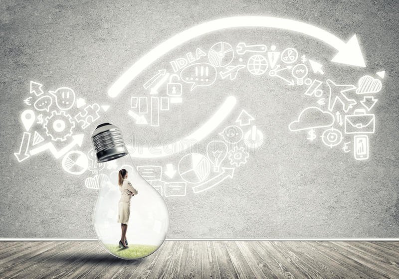 Businesswoman trapped in bulb. Businesswoman inside of light bulb in empty concrete room royalty free stock image