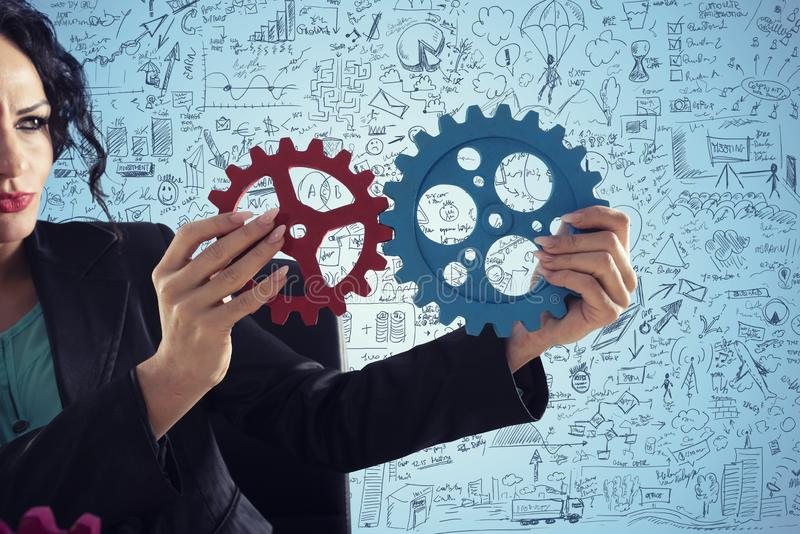 Businesswoman tries to connect gears pieces. Concept of Teamwork, partnership and integration royalty free illustration