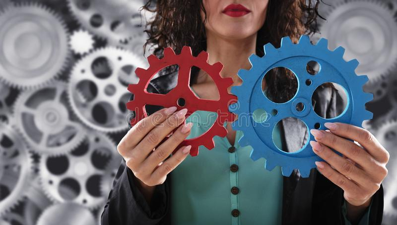 Businesswoman tries to connect gears pieces. Concept of Teamwork, partnership and integration. stock photo