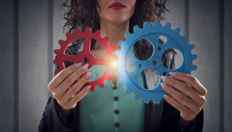 Businesswoman tries to connect gears pieces. Concept of Teamwork, partnership and integration. royalty free stock photo