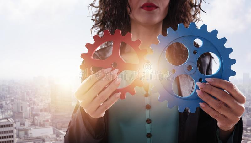 Businesswoman tries to connect gears pieces. Concept of Teamwork, partnership and integration. stock image