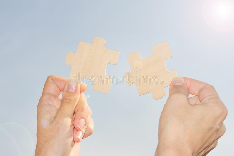 Businesswoman tries to solve the problem catching sun rays concept with jigsaw puzzle and hands stock photography