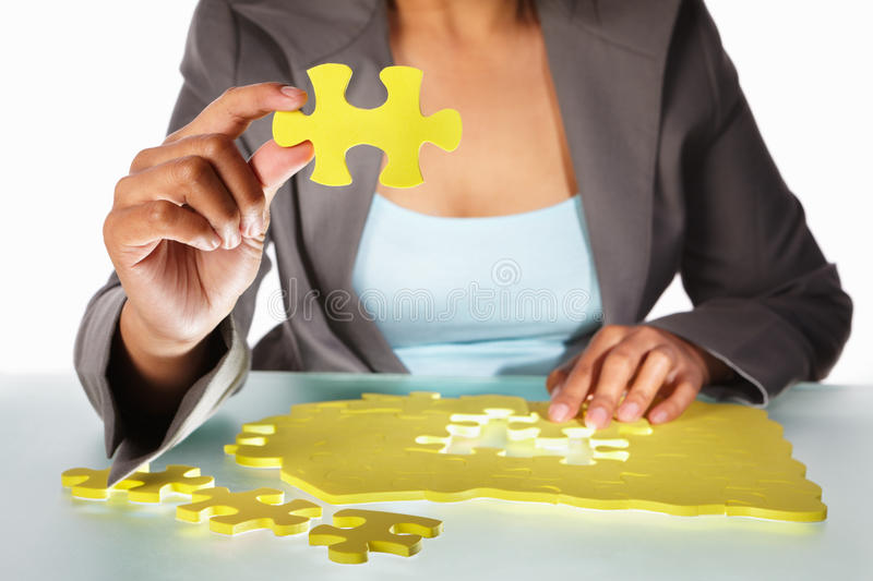Businesswoman trying to solve the puzzle. Unrecognizable Businesswoman trying to solve the puzzle royalty free stock photography